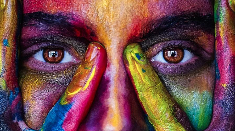 Close-up van twee bruine ogen met een gezicht met verf